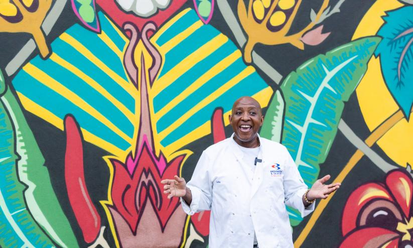 Glen from Glen's Kitchen standing in front of a brightly coloured garfitti mural, he is smiling with his hands out stretched palms up