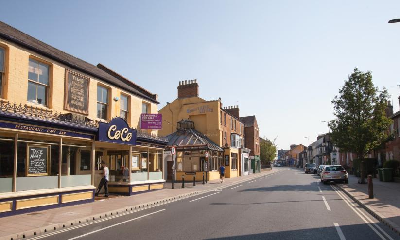 A view of a sunny street with cafes and a tree, this is Cowley Road in Oxford