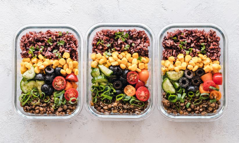three glass tupperware boxes fillied with beans, pulses, fruit; they're all look brightly coloured, green, yellow, reds, brown.