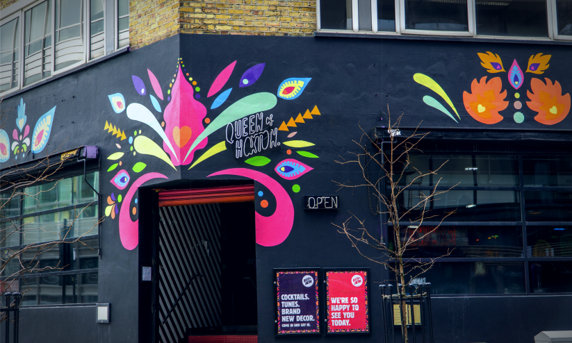 Brightly coloured frontage of The Queen of Hoxton, a roof-top bar in Shoreditch