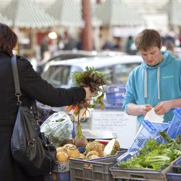 Woman in black coat holding bunch of carrots, stall seller wearing blue hoodie, preparing bag for the produce
