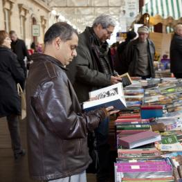 Two men flicking through books at a book stall